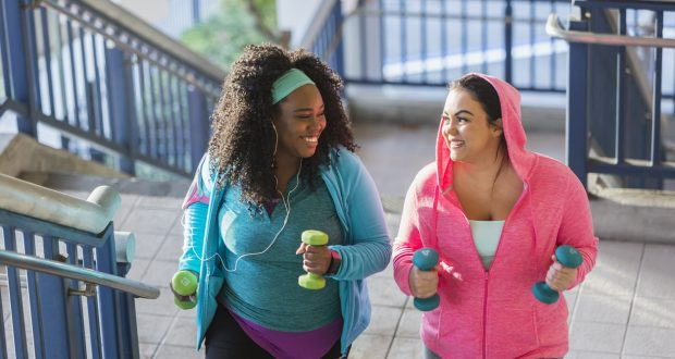 Two young women exercising, powerwalking up stairs