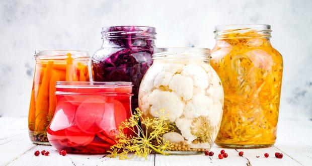 Sauerkraut variety preserving jars. Homemade red cabbage beetroot kraut, turmeric yellow kraut, marinated cauliflower, carrots and radish pickles Fermented food